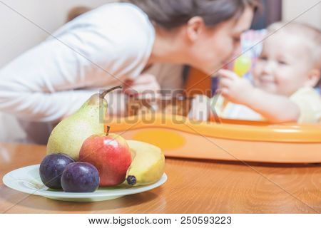 Mom Feeds The Baby Fruits Pure. Fruit. Nutrishion. Healthy And Natural Baby Food. Fruits Lying On Th