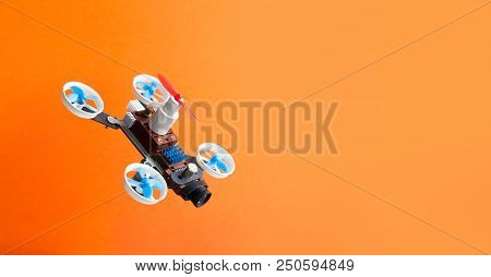Drone Multicopter With Camera On Orange Background. Creative Design Aerial Robotic Rotorcraft Mechan