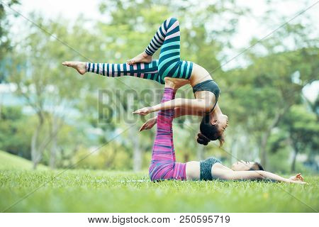 Side View Of Young Asian Women Practicing Acroyoga In Park, Female Base Lying On Grass With Raised U