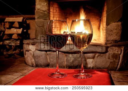 Chimney Place Wine Party Concept. Two Glasses Of Red White Wine, Fireplace Background. Romantic Xmas