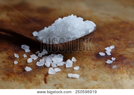 Himalayan Halite salt condiment macro view. Natural mineral flavoring food preservative, Saline sodium chloride white crystal in wooden spoon, aged rusty background. Shallow depth field poster