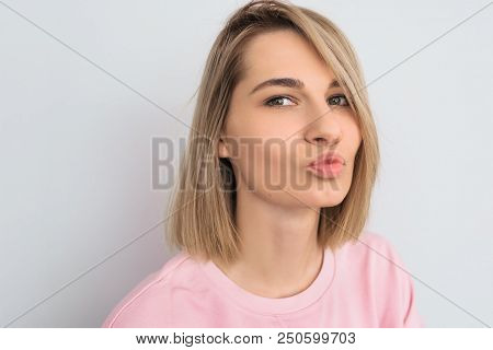 People And Beauty Concept. Portrait Of Cute Gorgeous Young Blonde Hair Female In Pink Clothes, Blowi