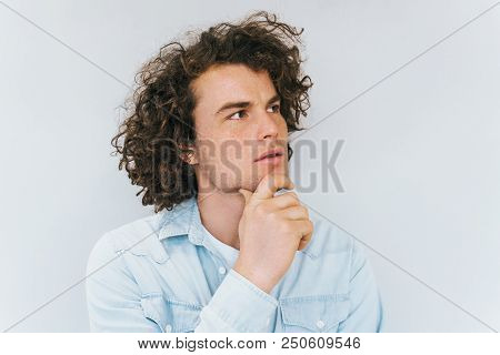 Studio Shot Of Handsome Pensive Male Model With Curly Hair, Wears Blue Shirt, Looking Up Thinking Ab