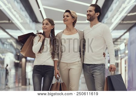 Happy Family Of Three In Modern Mall With Bags. Walking With Bags. Fashion Store. Buying In Boutique
