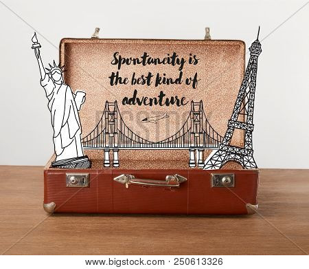 Open vintage travel bag with illustration and lettering - Spontaneity is the best kind of adventure poster