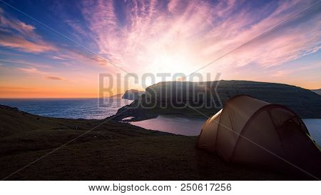 camping tent near a mountain lake with a beautiful sunset and sky