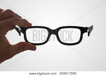 hand holding glasses between thumb and index finger, isolated on white