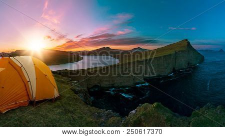 camping tent on an edge of a cliff with a beatiful sunset scene