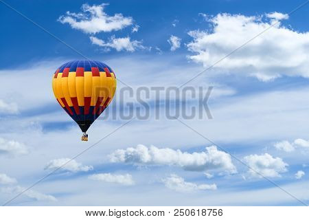 Hot Air Colorful Ballon Against Blue Sky With White Fluffy Clouds And Copyspace For Text
