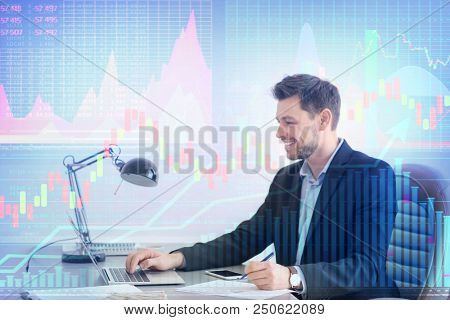 Double exposure of graphs and financial trader working with laptop at table in office. Forex concept poster