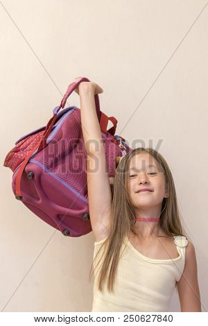 Funny Little Girl With Big Backpack Jumping And Having Fun Against White Wall. School Concept. Back