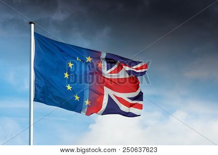 Merging European And British Flag In Front Of Dark Clouds In Sky As A Symbol For The Brexit