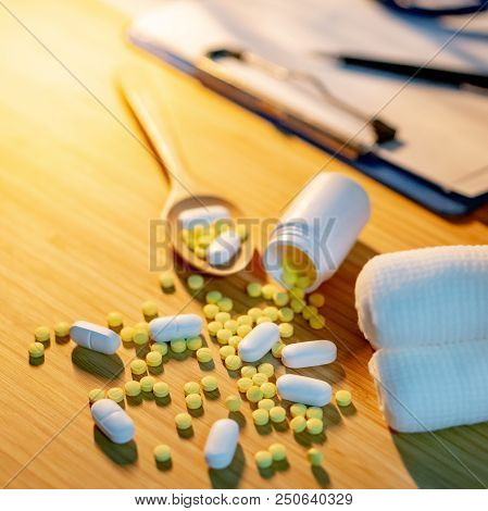 Pills spilling out of pill bottle with gauze bandage roll, pharmaceutical wooden spoon and clipboard on doctor desk. Prescription medicine or medical diagnosis and treatment concepts poster