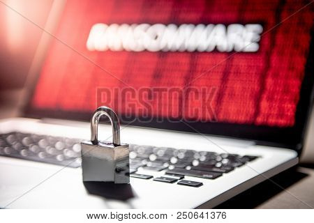 Padlock Or Lock On Laptop Computer With Red Binary Ransomware Attacking On Monitor Screen. Cyber Att