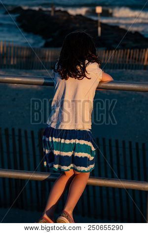 View Of Young Cute Little Girl On The Boardwalk With Back To Camera Looking Towards The Ocean Surf