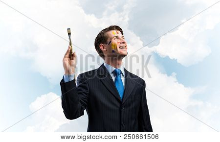 Horizontal shot of young and happy businessman in black suit holding paintbrush in his hand while standing against blue and cloudy skyscape on background. poster