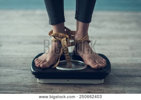 Close Up. Young Woman Standing On Weigher On Floor. Diet Concept. Weight Loss Problem. Starving Youn