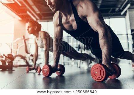 Young Man And Woman Training In Fitness Club. Man With Athletic Body. Healthy Lifestyle And Sport Co