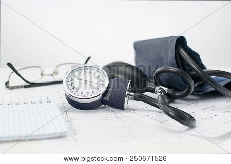 Sphygmomanometer On The Working Table Of A Cardiologist. Tonometer, Electrocardiogram And Notepad Fo