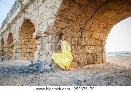 Young And Beautiful Caucasian Pregnant Woman In Her Early 30s Leaning On An Ancient Roman Aqueduct,