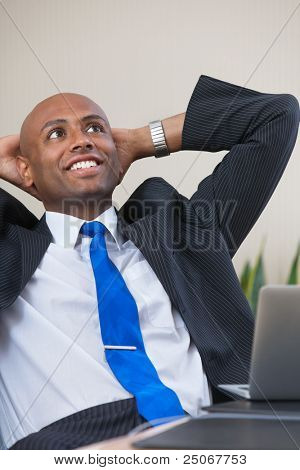 Relaxed Afro American business man sitting at his desk looking into the air poster