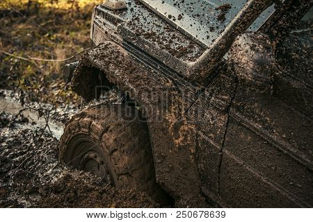 Fragment of car stuck in dirt, close up. Offroad tire covered with mud on nature background. Dangerous expedition concept. Wheel in deep puddle of mud overcomes obstacles. poster
