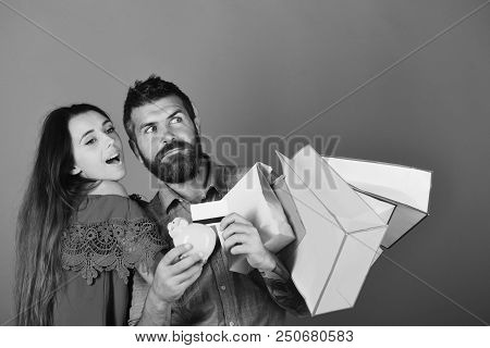 Money And Shopping Concept. Couple In Love Holds Shopping Bags On Red Background. Guy With Beard And