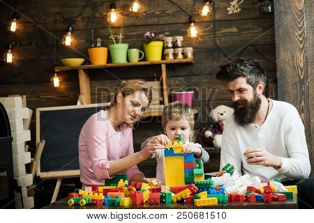 Game Concept. Learning Game. Son With Mother And Father Play Construction Game. Little Child Learnin