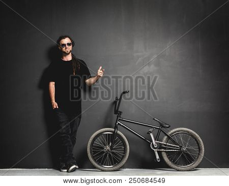 Man standing next to his BMX bike, pointing his finger. Dreadlocks and sunglasses. Leisure.