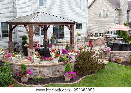 Colorful Exterior Curved Patio With Summer Flowers And Comfortable Wicker Armchairs Under A Covered