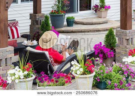 Man In A Straw Sunhat Sitting On A Recliner Chair Relaxing Reading On An Outdoor Patio Viewed Across