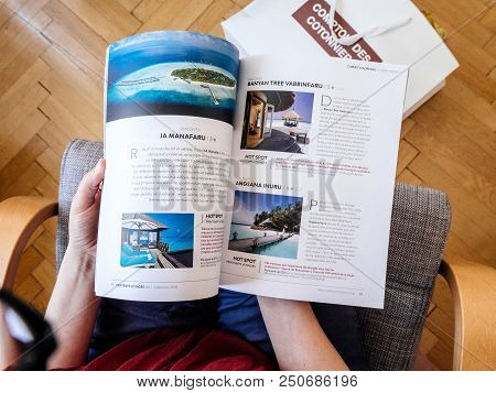 Paris, France - Jul 1, 2018: French Woman Reading On Wooden Office Table Travel Catalogue With Luxur