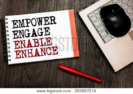 Conceptual hand writing showing Empower Engage Enable Enhance. Business photo showcasing Empowerment Leadership Motivation Engagement Bluetooth mouse on keyboard words red pen on wooden deck poster