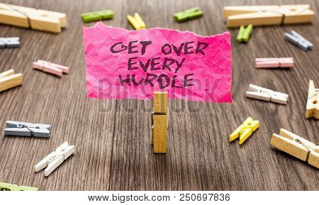 Conceptual hand writing showing Get Over Every Hurdle. Business photo showcasing Overcome any obstacle problem trouble adversities Paperclip hold pink note with texts many clips wooden floor poster