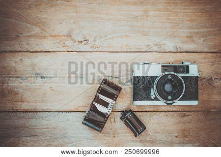 Photo of nostalgia - vintage film camera on old wooden background poster