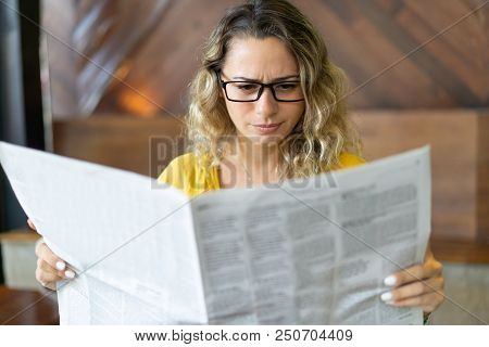 Frowning young woman reading job ads in newspaper. Displeased girl reading article in local newspaper in morning. Bad news concept poster