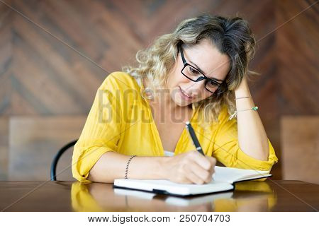 Hectic Young Woman In Glasses Writing Agenda For Meeting. Nervous Female Student Doing Homework At C