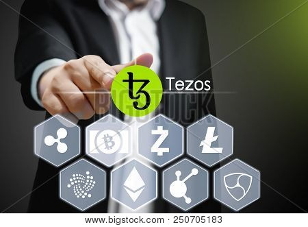 Concept Photo  Business Man Points His Finger At  Tezos Icon Cryptocurrency
