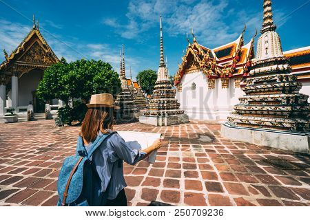 Young Woman Traveler With Backpack And Hat Looking The Map In Wat Pho At Bangkok Thailand. Traveling