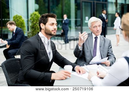 Young and senior businessmen in suits having business talk with one of colleagues outdoors