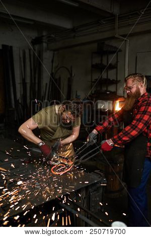 Two blacksmiths processing spiral molten metal workpiece with electric handtool on anvil poster