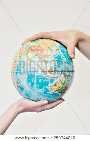 Two Hands Holding Globe On White Background. The Globe Is In The Palm