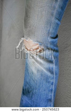 Woman Leg Wearing Jeans Torn Denim Against White Wall Background.