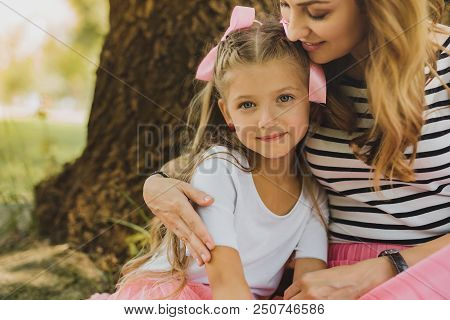 Beaming Mother. Happy Beaming Mother Hugging Her Cute Pleasant Girl While Sitting Near Tree In The P