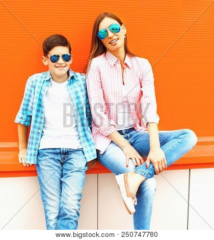Fashion Mother With Son Teenager In A Sunglasses, Checkered Shirts On A Orange Background
