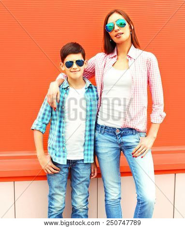 Fashion Mother With Son Teenager In A Sunglasses, Checkered Shirts On Orange Background