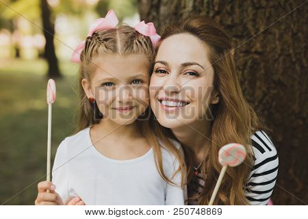 Holiday Together. Happy Beaming Mother And Daughter Feeling Relaxed While Eating Sweet Lollipops On