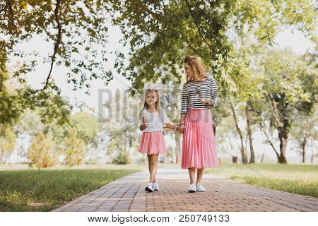 Joining Mother. Blonde-haired Cute Daughter Joining Her Mother In The Park On Nice Warm Sunny Day