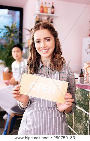 Beaming Woman. Appealing Beaming Young Woman Smiling Broadly While Enjoying Working As Waitress