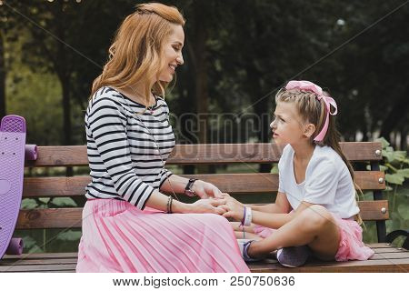 Having Conversation. Cute Preschool Daughter Having Nice Conversation With Her Appealing Mother